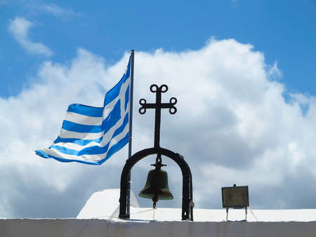 EU: The Greek National flag near cross of small church against blue cloudy sky background