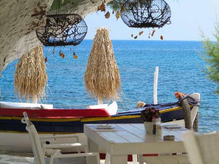 hotel resort: Cafe on sea coast concept - tables, umbrellas, decorations and blue horizon Stock Photo