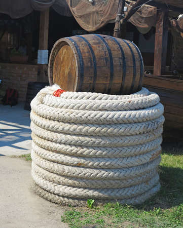 barrels: Old brown barrel and white rope over fishing nets background