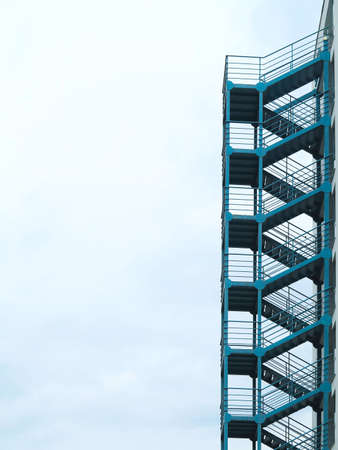 Green outside fire escape stairs ladder over cloudy sky background