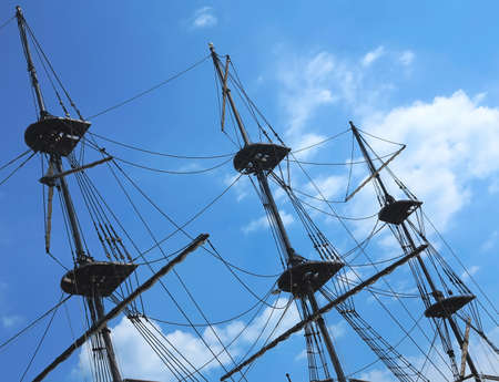 masts: masts and rigging of a old sailing ship over blue sky background