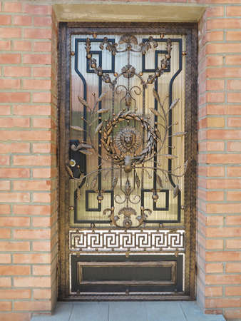 Forged bronze decorative door gate over brick wall background. Stock Photo