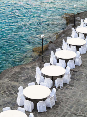 restaurant tables: Open air restaurant near sea- white chairs and tables
