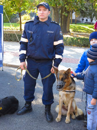 sniffer: 14.10.2016, Moldova, Chisinau: Policeman with police dog and children in park Editorial