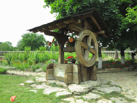 Vintage old wooden water well with huge giant wheel