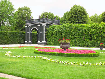 Abstract black garden arbor, flower beds and shorn trees in a well-kept park