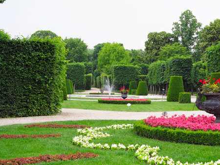 Abstract ideal flower beds and shorn trees in a well-kept park