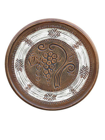 Old handmade ornated brown pottery plate isolated on white background