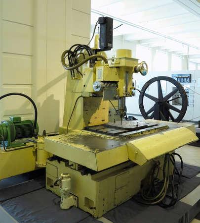 Old and powerful industrial metalworking machine in vintage workshop