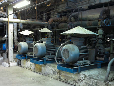 Industrial big water pumps with electric motors, pipes, tubes, equipment and steam turbine at modern power plant