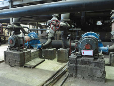 Grandi pompe idrauliche industriali con motori elettrici, tubi, tubi, attrezzature e turbine a vapore in una moderna centrale elettrica