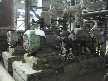 Industriële grote waterpompen met elektromotoren, pijpen, buizen, apparatuur en stoomturbine bij moderne elektriciteitscentrale