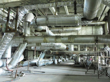 Giant glitter tubes, equipment, cables and piping inside of a modern industrial power plant