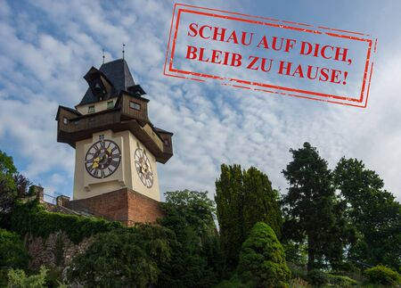 The clock tower (Grazer Uhrturm) on Shlossberg hill, famous tourist destination in Graz, Styria region, Austria, with text in german