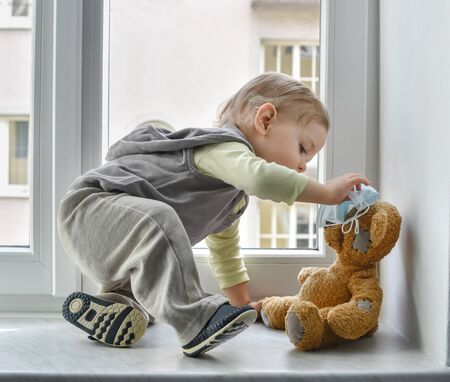 Child in home quarantine playing at the window with his sick teddy bear wearing a medical mask against viruses during coronavirus and flu outbreak. Children and illness COVID-2019 disease concept