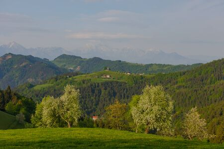Slovenian breathtaking landscape with Julian Alps and charming little church of Sveti Tomaz (Saint Thomas) on a hill. Beautiful spring in the mountains, in Slovenia.