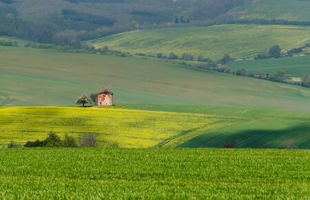 Rural abstract landscape with rolling hills and windmill in South Moravia, Czech Republic Banque d'images
