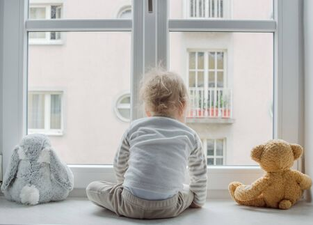 Cute boy at home looking through the window and playing with his toys