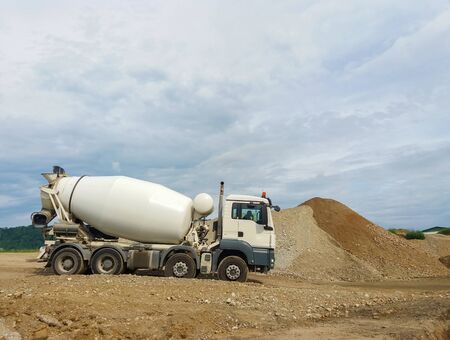 Concrete mixer truck working on construction site.