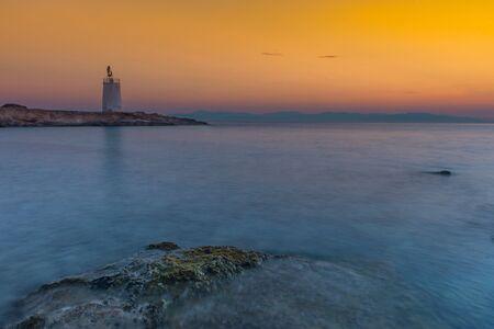 Old small lighthouse of the Aegina island, Saronic gulf, Greece, at sunset.