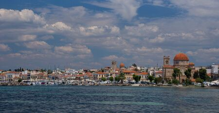 Clear waters of Mediterranean sea and a beautiful view of Aegina town in Aegina island, Saronic gulf, Greece.