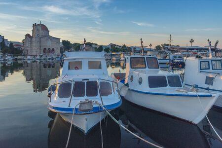 Port of Aegina town with yachts and fishermen boats docked in Aegina island, Saronic gulf, Greece, at sunrise. Stock Photo
