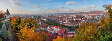 Cityscape of Graz and the clock tower (Grazer Uhrturm), famous tourist attraction on Shlossberg hill, Graz, Styria region, Austria, in autumn. Panoramic view