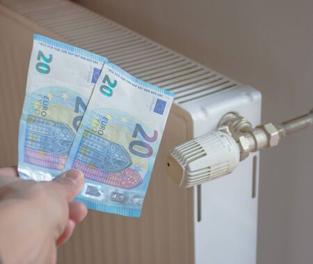 Energy efficiency concept with radiator and euro currency – the cost of thermal energy is more expensive. Selective focus.