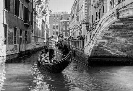 Venice, Italy - April 20, 2019: Venetian canal with gondolas and historic houses, in a beautiful sunny day.