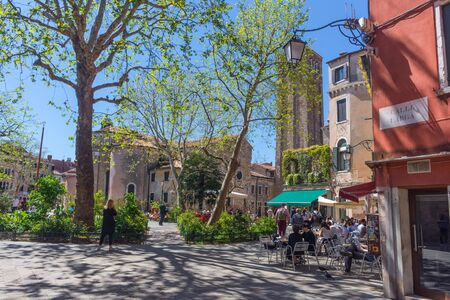 Venice, Italy - April 20, 2019: Beautiful square with terraces, restaurants and old church, in a beautiful sunny day.