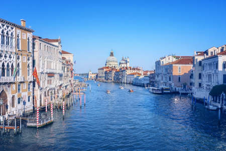 Beautiful Venetian view with boats on Grand Canal and Basilica Santa Maria della Salute, in Venice, Italy, in pastel colors.