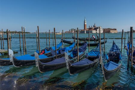 Gondolas near Saint Mark square (San Marco) and San Giorgio di Maggiore church in the background, in Venice, Italy