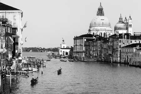 Beautiful Venetian view with Grand Canal, Basilica Santa Maria della Salute and traditional gondolas, in Venice, Italy (black and white retro style)