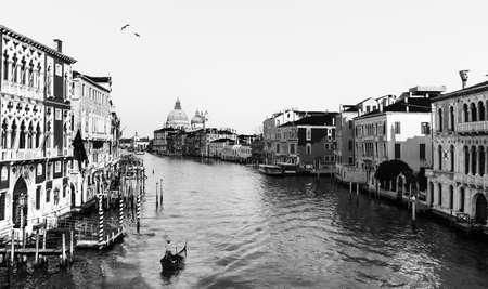 Beautiful Venetian view with Grand Canal, Basilica Santa Maria della Salute and traditional gondolas, in Venice, Italy (black and white old retro style photo)