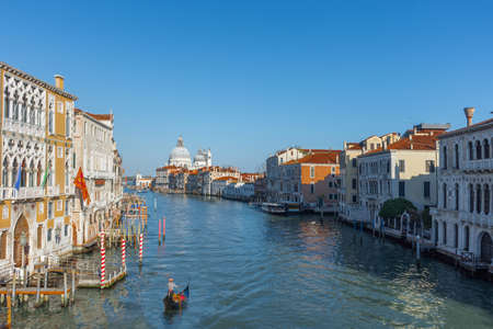 Beautiful Venetian view with Grand Canal, Basilica Santa Maria della Salute and traditional gondolas, in Venice, Italy