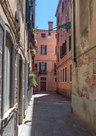 Narrow street with historic houses in Venice, Italy, in a beautiful sunny day.
