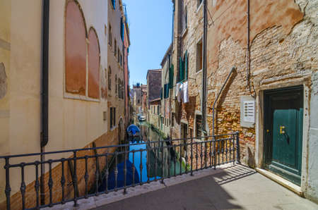 Narrow canal in Venice, Italy, with boats and historic houses, in a beautiful sunny day. Stock fotó