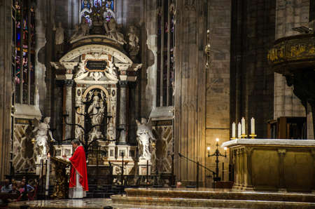 Milan/Italy-July 09, 2016: Priest preaching at the altar of Milan Cathedral, one of the biggest gothic cathedrals and famous tourist attraction in Lombardy, Italy Publikacyjne