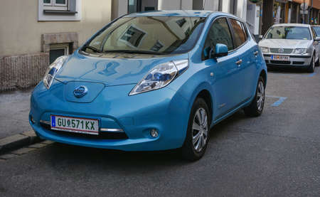 Modern electric car blue color Nissan parked on the street. New energy vehicle, environment friendly car