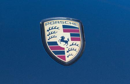 Porsche logo close up on a blue car