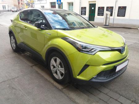 Modern hybrid car green color Toyota parked on the street. New energy vehicle, environment friendly car Redakční