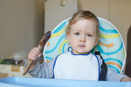 Cute baby child getting messy eating cereals or porridge by itself, with a wooden spoon