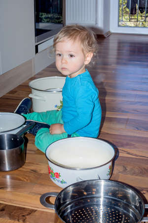 Cute little boy sitting on the kitchen floor playing with cooking pots and making a lot of noise 免版税图像