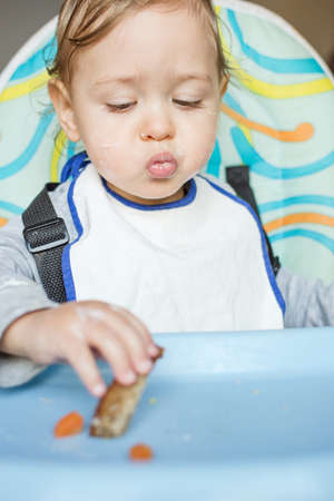 Cute baby child eating by itself and not liking the food