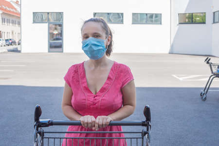Woman wearing a medical mask standing with an shopping cart in front of a store during coronavirus Covid-19 pandemic.