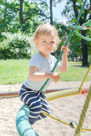 Cute little child having fun playing in the park, beautiful summer sunny day in children playground