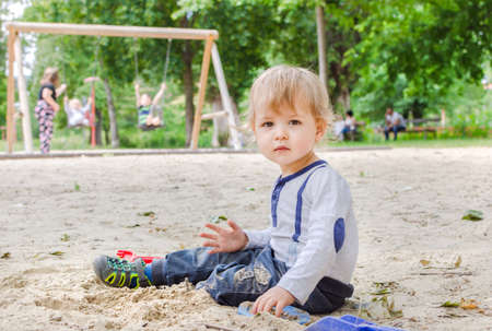 Happy little child having fun playing with sand and colorful toys in the park, beautiful summer sunny day in children playground