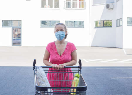 Woman wearing a medical mask standing with an almost empty shopping cart in front of a store during coronavirus pandemic. Concept of economic crisis affecting people due to COVID-2019 disease
