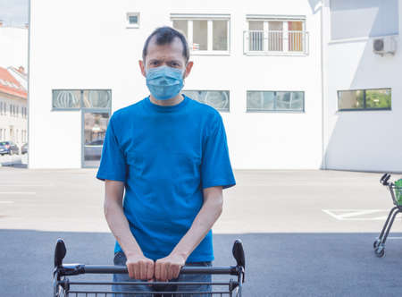 Man wearing a medical mask standing with an shopping cart in front of a store during coronavirus Covid-19 pandemic.