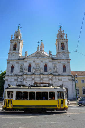 Vintage yellow tram and the Estrela Basilica (or Royal Basilica and Convent of the Most Sacred Heart of Jesus), in Lisbon, Portugal